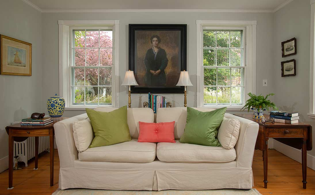 Sitting room of the Village Inn Cape Cod with modern couch and pillows with a painted portrait of a woman on the wall