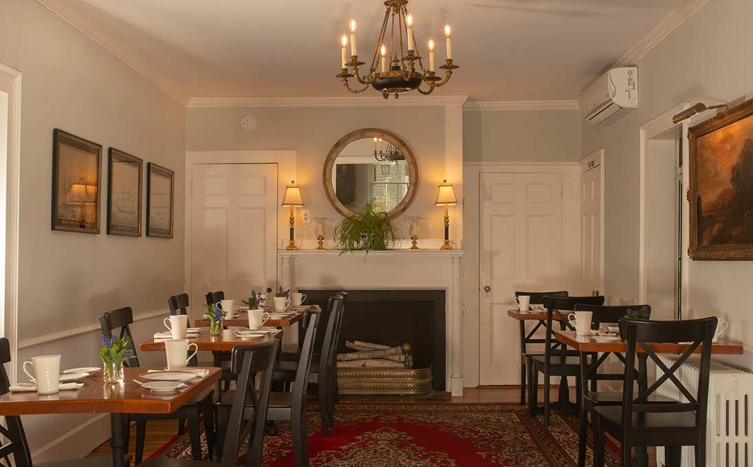 Indoor traditional dining room with five separate tables, fireplace and chandelier