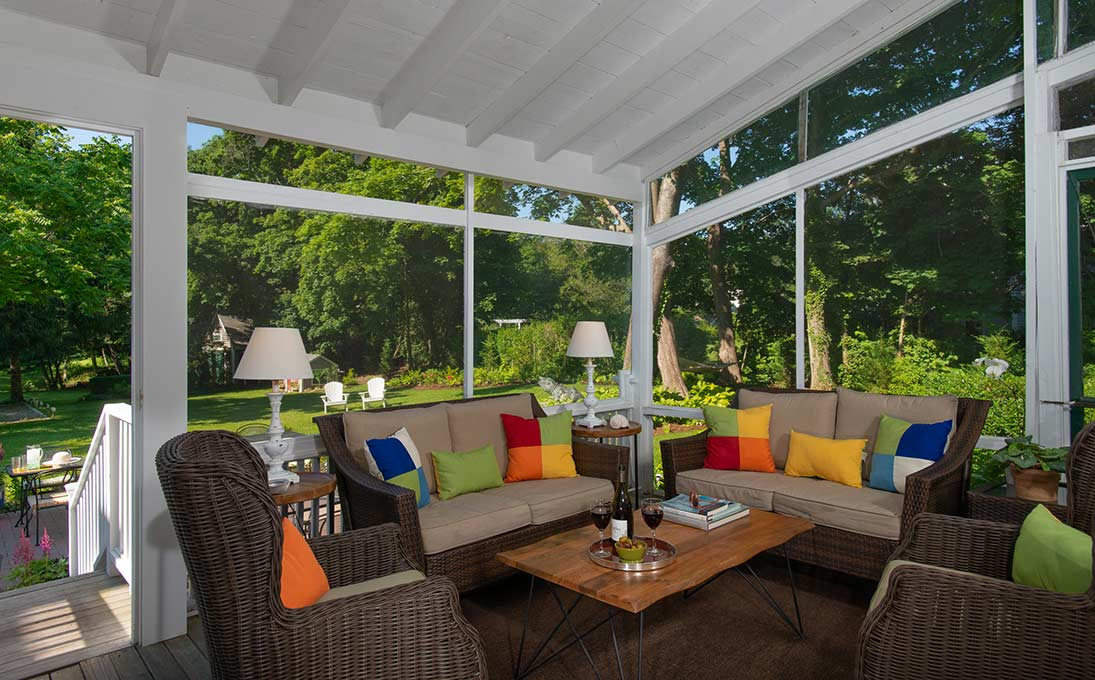 Screened in porch with garden views, rattan furniture including two couches and two seats with colorful pillows, as well as a table with wine being served
